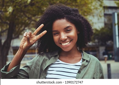 Charming young woman making peace gesture