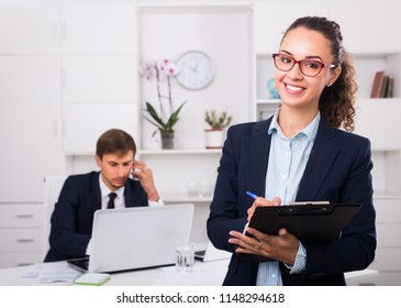 charming young woman manager holding cardboard and smiling in office