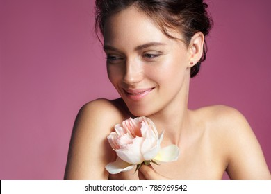 Charming young woman with perfect makeup. Photo of brunette woman with rose on pink background. Skin care concept