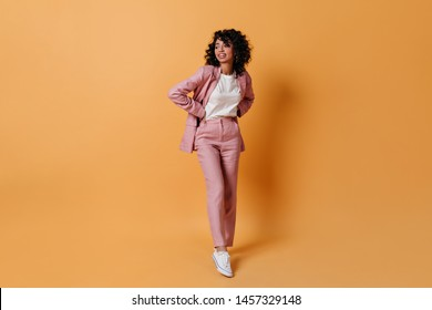 Charming young woman in pink suit looking away. Full length view of smiling girl posing on yellow background.