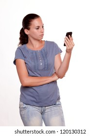 Charming young woman reading a message on cellphone screen standing over white background