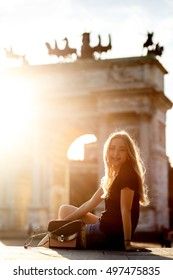 Charming young woman sits in the front of Arch of Peace in Milan