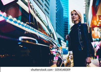 Charming young woman strolling outdoors on shopping streets and enjoying showplaces during vacantion.Good looking female tourist waiting transfer to destination standing in urban setting