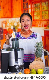 Charming young woman in traditional andean dress standing inside kitchen inserting apple pieces into juice maker, healthy lifestyle concept