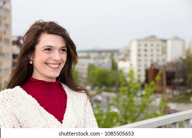 Charming young woman in white cardigan. Shooting has been in the spring city near the Roses Valley Park.