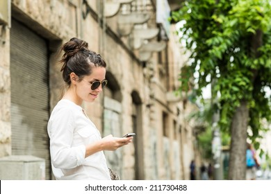 Charming young woman in white shirt reads or texts message to mobile phone, against old grunge houses in old city.
