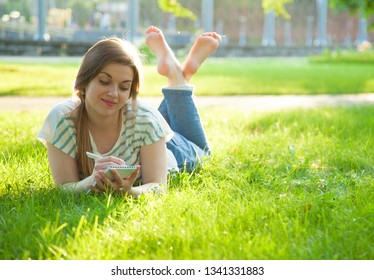 Charming young woman writing in a diary on a sunny lawn in a park
