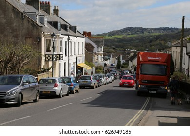 Charmouth, Dorset, England, UK. April 14 2017. Typical main street in an English Town showing different periods of architecture and background hills.