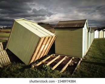 CHARMOUTH, DORSET, UK - November 3 2019: Storm damage - beach hut blown over by high winds.