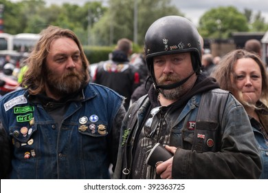 CHARNOCK RICHARD SERVICES, LANCASHIRE, ENGLAND - JUNE 24, 2012: Two men dressed in motorcycle gear at a the North West Euro Demo Run. One is wearing an old open faced helmet.