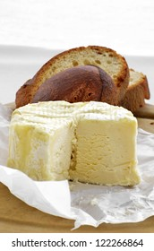 Charouce / Brillat Savarin soft french cheese in waxed paper on a board with slices of rustic french bread