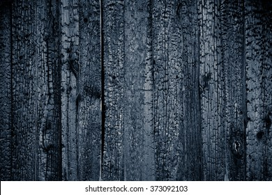 Charred black wooden wall with copy space. Abstract background with a burned boards textures closeup