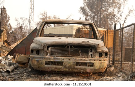 Charred car next to chain link fence in front of home burned to the ground in the recent wild fire fire storm in Redding, CA. Smoke and ash in the air as the fire continues to burn several miles away.