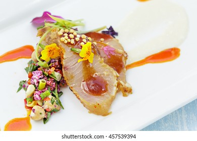 Charred Hamachi seasoned with togarashi and garnished with edible flowers, macadamia nuts and sauce