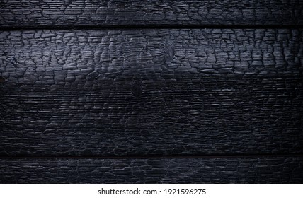 charred log background texture. burnt wood texture, Burned scratched hardwood surface. Smoking wood plank background panorama banner. Smoking wood halloween banner background