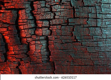 Charred wood texture, painted with light, red and turquoise.