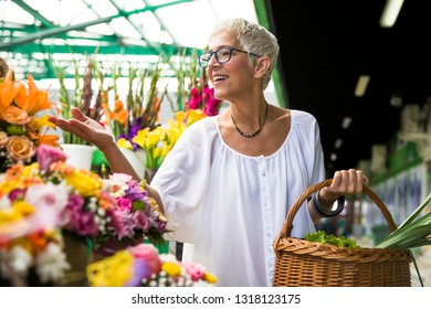 Charrming senior woman buying  flowers on local market
