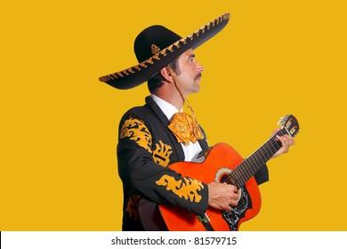 Charro Mariachi man playing guitar on yellow background