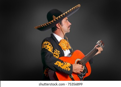 Charro Mariachi playing guitar on black background [Photo Illustration]