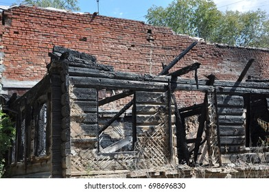 Charry corner of a burnt house with ruined wooden framework against a red brick wall with green trees and the blue sky.