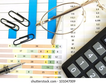 Chart with calculator, glasses and pen