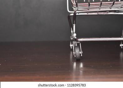 Chart from grocery store on the wooden background. Empty shopping trolley. Business ideas and retail trade. Advertising of food products. Selective focus.