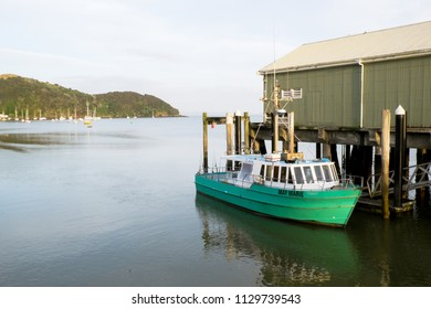 Charter fishing vessel tied up at Mangonui wharf harbour with anchored boats in background, Far North District, New Zealand, NZ