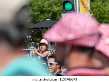 Chartres, France - July 13, 2018: A sweet little girl on her fathers shoulders is cheering the cyclists in Chartres during the longest stage, Fougeres-Chartres, of Le Tour de France 2018.