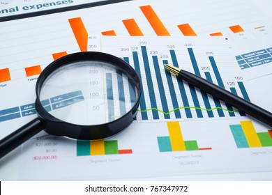 Charts and Graphs paper, magnifying glass and pen. Financial, Accounting, Statistics, Investment, Analytic research data and Business company meeting concept