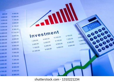 Charts and tables with calculator and the word Investment
