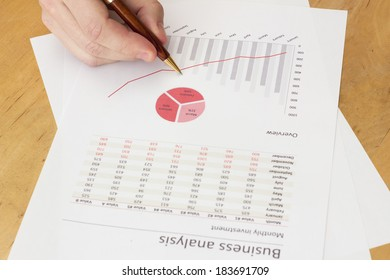 charts at workplace. Hand holding a pen and red charts
