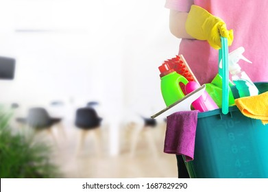 Charwoman standing with a bucket and cleaning products on blurred office background.