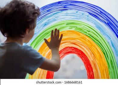 Chase the rainbow. child at home draws a rainbow on the window. Flash mob society community on self-isolation quarantine pandemic coronavirus. Children create artist paints creativity vacation