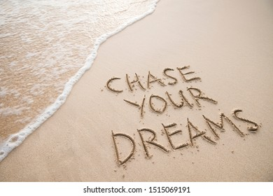 Chase Your Dreams travel message handwritten on smooth sand beach with incoming tropical wave