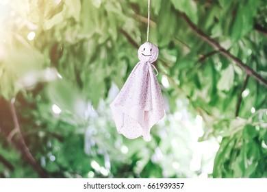 Chasing rain doll hanging on branches tree, Rainy season come