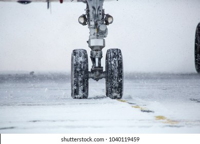chassis airplane close-up in winter in snow. Close-up of chassis of passenger airliner in the snow on airport platform.