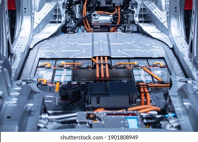Chassis of the electric car with powertrain and power connections closeup. Blue toned. EV car drivetrain at maintenance