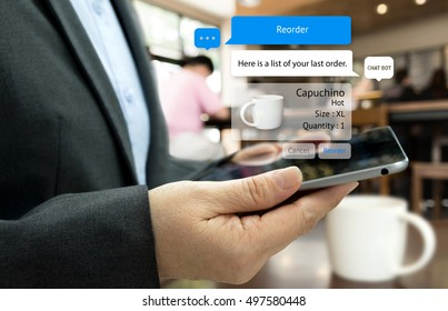 Chat bot and future marketing concept . Customer hand holding tablet for reorder coffee and popup out tablet screen with automatic chatbot message screen , coffee shop background