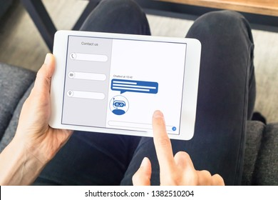 Chatbot with artificial intelligence technology (AI) internet virtual assistant on digital tablet computer screen, online customer support website or social media network, woman at home