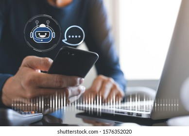 Chatbot assistant conversation, Ai Artificial Intelligence technology concept. Casual business man chatting with chatbot via mobile smart phone application while working on laptop computer