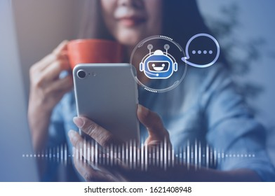 Chatbot assistant conversation, Ai Artificial Intelligence technology concept. Casual business woman chatting with chatbot via mobile smart phone application while working on laptop computer