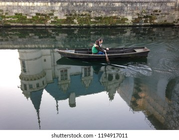 Chateau of Azay-le-Rideau, Loire Valley, France - December 29, 2016. Frosty winter day does not stop tourists from visiting the chateau. Two people canoeing in the river near chateau