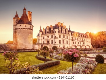 The Chateau de Chenonceau at sunset, Loire Valley, France. This castle is one of the main tourist attractions in Europe. Beautiful scenic view of the old castle with a flower garden in sunlight.