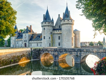 Chateau de Sully-sur-Loire, France. This medieval castle located in the Loire Valley is a famous travel destination in Europe. Scenic view of the old castle or palace with a bridge at sunset.