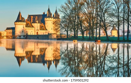Chateau de Sully-sur-Loire in the sunset light, France. It is a famous landmark of the Loire Valley. Beautiful sunny view of the medieval castle with reflections in water. Old fortress in summer
