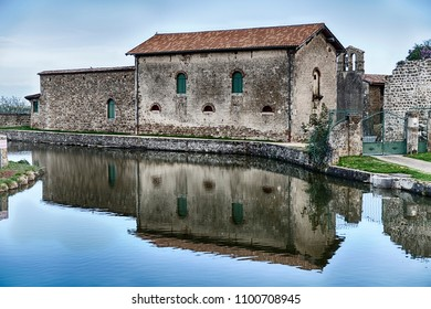 Chateau de Virieu is an old stone chateau with strong reflections from a small pond in the town of Peulussin in France.