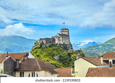 Chateau Fort of Lourdes. Castle on a rock. Snowy mountain peaks. Blue sky with white clouds. City in the Hautes-Pyrénées, France