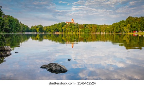 Chateau Konopiste at the sunset reflected in the water with rock foreground, Central Bohemia, Czech Republic.tourist