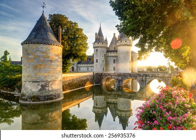 Chateau of Sully-sur-Loire in the sunset light with lens flares, France. It is a famous landmark of the Loire Valley. Beautiful sunny view of medieval castle with reflections in water in summer.