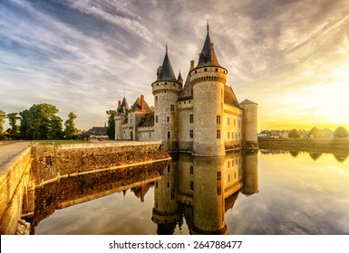 Chateau of Sully-sur-Loire at sunset, Loire Valley, France. Scenic view of medieval castle with reflection in water in sun light. Loire Valley is the UNESCO Site. Beautiful sunny scenery in evening.